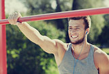 happy young man with earphones and horizontal bar