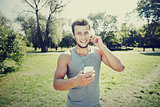 happy man with earphones and smartphone at park