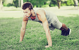 young man doing push ups on grass in summer park