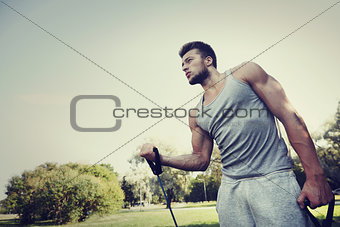 young man exercising with expander in summer park