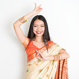 Young girl in Indian sari dress dancing