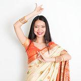 Young girl in Indian sari dress dancing