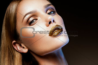 Beautyful girl with gold glitter on her face
