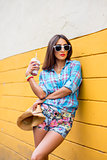 Woman in the city on the background yellow wall, holding milkshake, fresh juice in glasses, wearing shirt with the bracelets her arm, makiyah sensual red lips, recreation concept lifestyle. Happy enjoying.