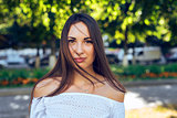 Close-up portrait of beautiful brunette girl, standing in the park, summer, white blouse, long hair, sensual look, the concept  student, fashion lifestyle, rest in a  .