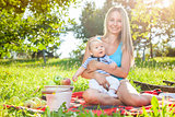 Beautiful mother with baby sitting outdoors on a blanket