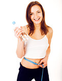 young girl measuring herself in studio isolated on white background happy smiling, holding bottle of water wearing sport clothers, lifestyle people concept
