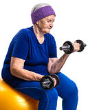 Senior woman working out with with dumbbells while sitting on fitball