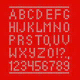 Embroided by cross stitch english alphabet with numbers and symbols on red cloth texture.