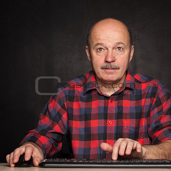 man in a white shirt works at the computer, typing text