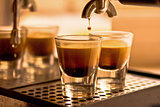 A shot of coffee pouring into two espresso cups