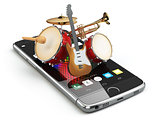 Mobile phone and musical instruments. Guitar, drums and trumpet.