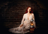 Portrait of sexy sad redhead girl with kerosene lamp