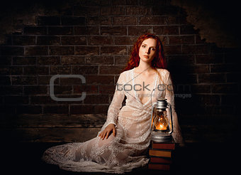 Portrait of sexy sad redhead girl with kerosene lamp