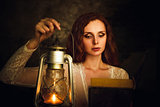Beautiful red-haired young woman with kerosene lamp reading book