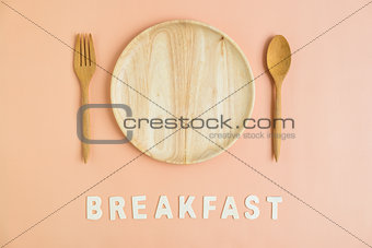 Top view of wooden cutlery with breakfast word
