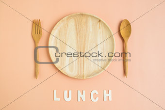 Top view of wooden cutlery with lunch word