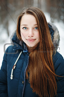 Beautiful woman in winter clothes standing in winter par