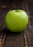 Green organic healthy apple on wooden board