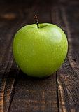 Green organic healthy apple on wooden board