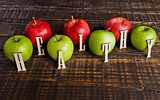 Green and red organic healthy apples on wooden board