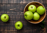 Green organic healthy apples in bowl on wooden board