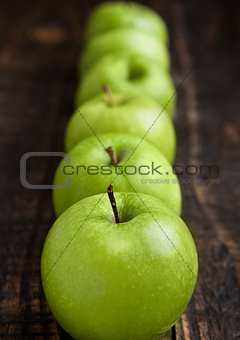 Green organic healthy apples on wooden board
