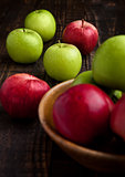 Green and red organic  apples in bowl on wooden board