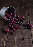 Frozen berries mix in a black bowl on wooden background