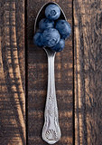 Blueberries on old spoon on grunge wooden board