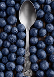 Blueberries around spoon close up photo