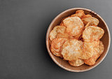 Bowl with potato crisps chips on black stone board