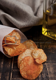 Bowl with potato crisps chips and olive oil on wooden board