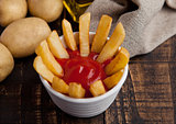 Fried french fries chips in fryer with ketchup on wood