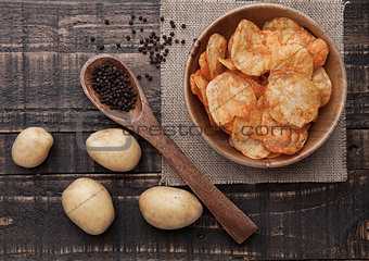 Bowl with potato crisps chips with pepper on wood