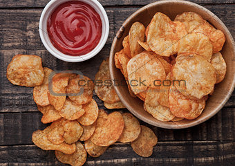 Bowl with potato crisps chips and ketchup on wooden board