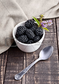Blackberry in white bowl and spoon on grunge wooden board