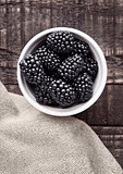 Blackberry in white bowl  on grunge wooden board