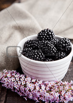 Blackberry in white bowl and flowers on wooden background