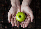Green healthy apple in human arms on wooden background