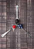 Raspberry blueberry and blackberry on spoon and wooden table