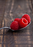 Raspberries on old spoon on grunge wooden board