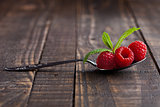 Raspberries on old spoon and mint on grunge wooden board