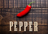 Red hot mexican pepper on wooden board with letters