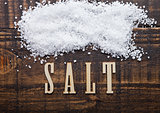 Salt on grunge wooden board with letters below