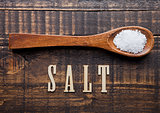 Salt on wooden spoon with letters below