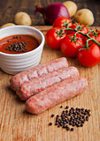 Raw beef sausages with tomatoes and sause on board
