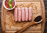 Raw beef sausages with pepper spoon and sause on board