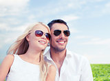 happy couple in shades over natural background