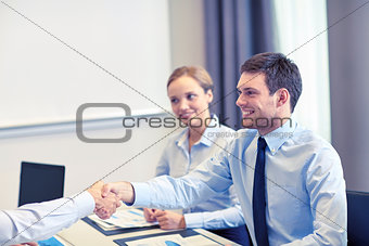 smiling business team shaking hands in office